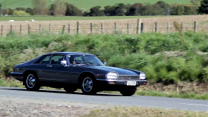 Jaguar XJS driving on a country road